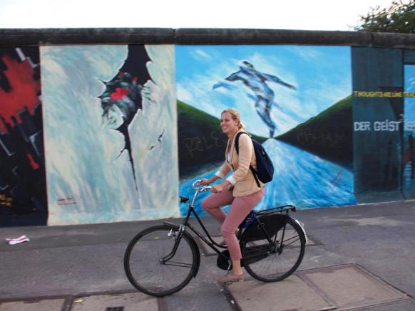 Sanne Boersma fietst langs de East Side Gallery